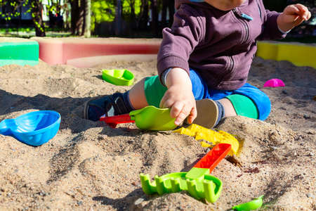 Unrecognizable little caucasian boy sitting in sandbox with toys on sunny summer day in big city. Child reaches for the bright plastic sand scoop.