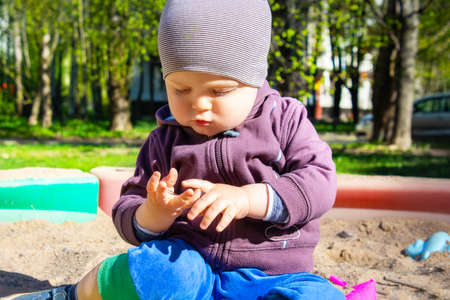 Cute little caucasian boy sitting in sandbox with toys on sunny summer day in park . Child looking at something in his palm, dressed in sweatshirt and striped hat.
