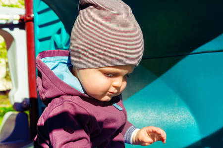Cute little caucasian boy sitting at childrens play complex. Baby sits inside blue plastic tubein. Sunny summer day in city. Dressed in sweatshirt and striped hat.
