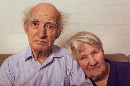 Very old grandma and grandpa cuddling on couch. Love in old age. Wife puts her head on husbands shoulder. Elderly people. Standard-Bild