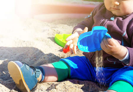 Unrecognizable little caucasian boy sitting in sandbox with toys on sunny summer day in big city. Child holding a blue sand mold.