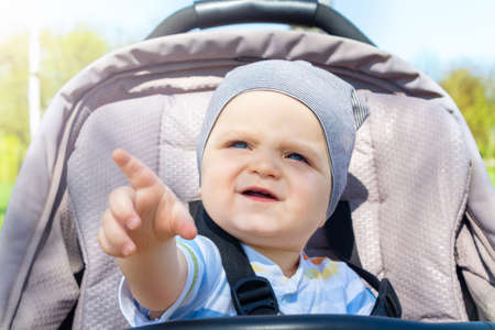 Adorable happy caucasian baby boy sitting in grey stroller in park and pointing with finger at something . Summer day. Child is strapped in stroller during the walk.