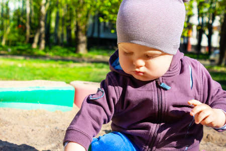 Cute little caucasian boy sitting in sandbox with toys on sunny summer day in park . Child looking at something in his hand, dressed in sweatshirt and striped hat.