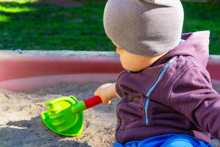 Cute little caucasian boy sitting in sandbox with toys on sunny summer day in park . Child holding sand scoop in his hand, dressed in sweatshirt and striped hat.