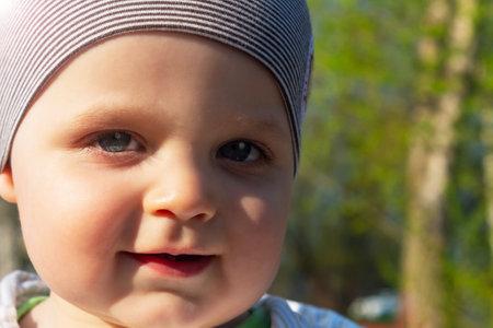 Cute caucasian baby boy in park. Close-up photo. Summer sunny day. Suns lights falling on child face. Standard-Bild