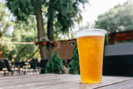 Light beer in glass on wooden table.