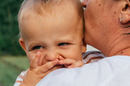 Little boy looks over his mothers shoulder. Standard-Bild