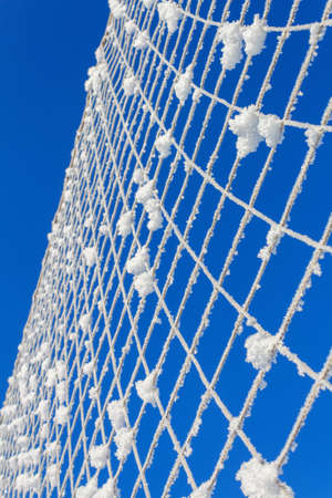 Volleyball net covered with snow. Natures minimalism.