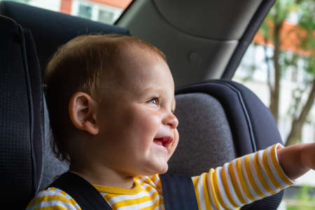 Happy baby boy sitting in car seat.