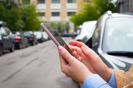 Woman holding mobile phone and booking cab.