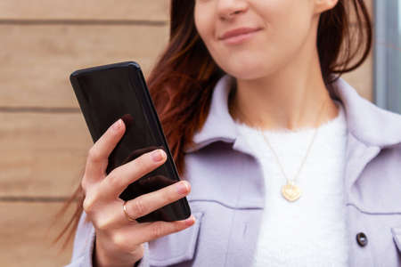 Woman holding mobile phone in hand.