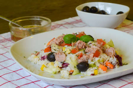 Dish of rice salad with tuna, corn and black olives photo