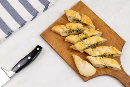 Baked and sliced bruschetta bread with garlic and spices served on the wooden board.