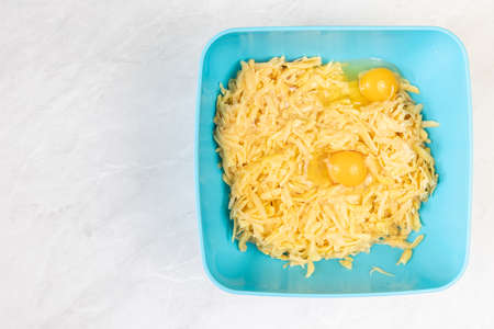 Grated raw potatoes with eggs in the bowl.