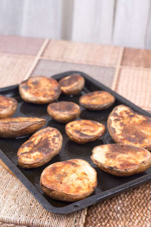 Baked potatoes with shell in the oven. Banque d'images - 144170003