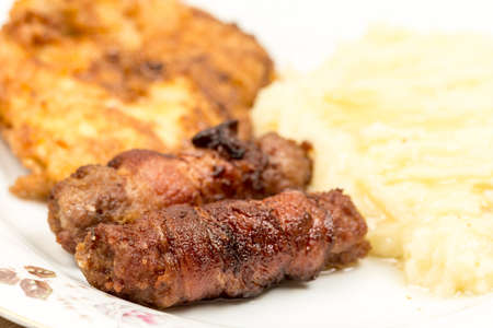 Grilled kebabs with bacon and pork steak with mashed potatoes.