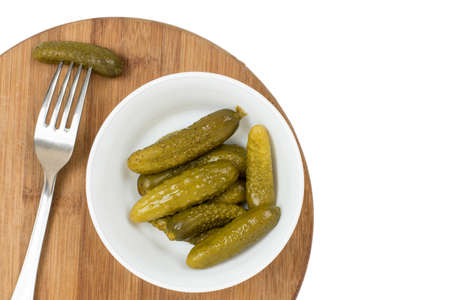 Pickles in the bowl and pickle on the fork. Imagens