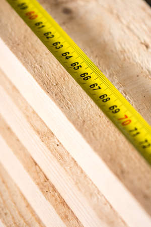 Construction meter on the pile of wooden planks. Standard-Bild
