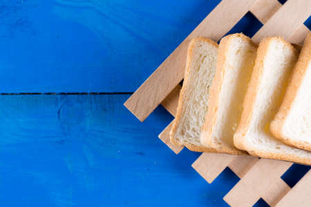 Toast bread slices on the blue wooden planks board.