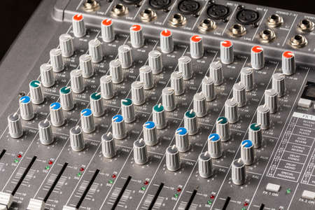 Audio mixing console with sliders and knobs on the channels