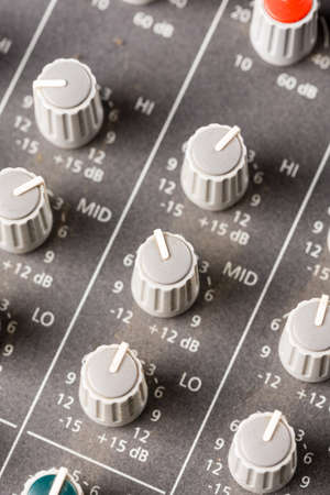Closeup macro audio mixing console knobs and sliders