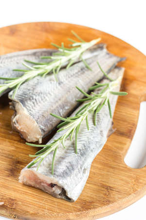 Fresh raw hake fish with rosemary branches on the round wooden board.