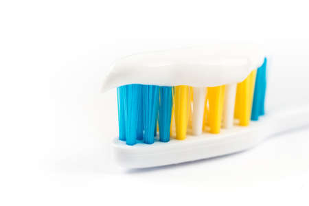 Closeup macro toothpaste on toothbrush isolated over white background.