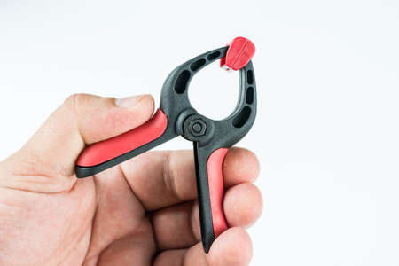 Plastic carpenters pinch tool in the hand above white background with copy space.