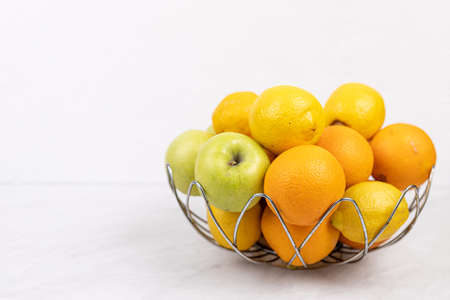 Basket with fruits above white background.