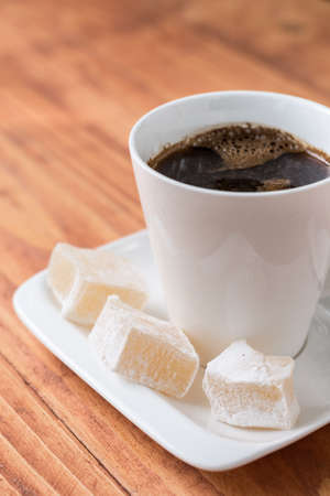 White cup of coffee on the wooden table with turkish delight on the plate.