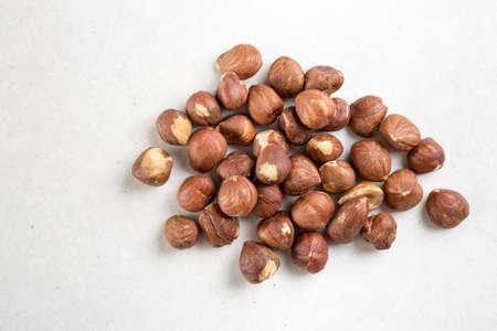 Pile of raw hazelnuts isolated above white marble stone.