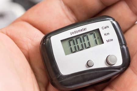 Hand holding black plastic pedometer