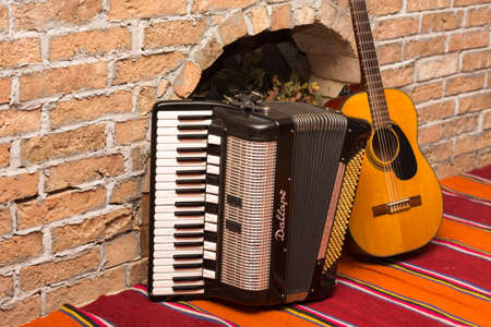 Accoustic guitar on the brick wall and accordion.
