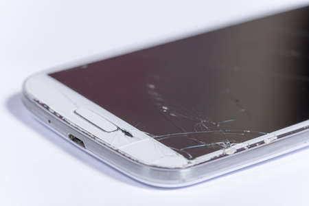 Crashed lcd touch screen on the white mobile phone.