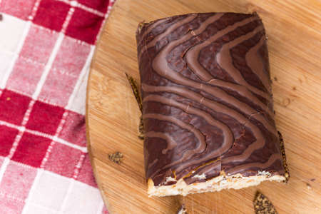 Sliced chocolate roll cake on the wooden board.