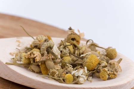Close macro view of chamomile tea in the spoon.