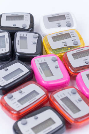 Pile of colorful pedometers over white background. Banque d'images