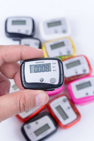 Digital pedometer in the hand over pile of pedometers. Banque d'images