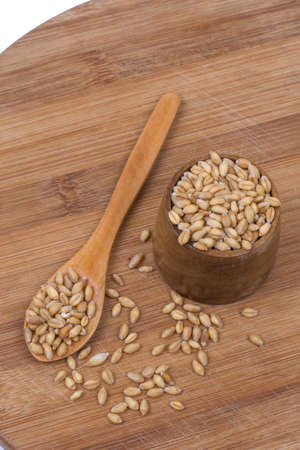 Wooden spoon with a bowl of wheat grains.