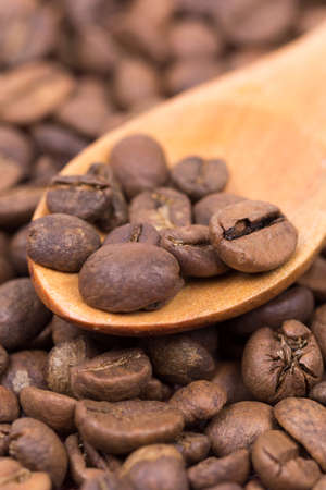 Coffee beans on the wooden spoon macro closeup.
