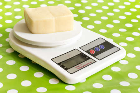 Yellow cheese on the kitchen digital scale 免版税图像