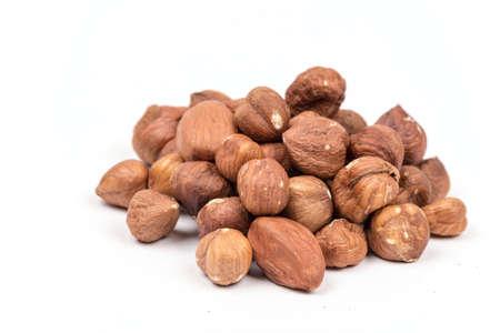 Pile of raw hazelnuts over white background