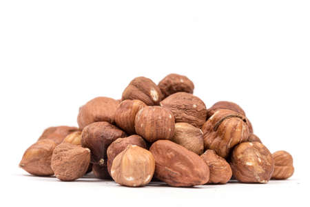 Pile of hazelnuts with copy space over white background