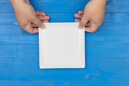 Empty white square plate in the hands above blue background with copy space.