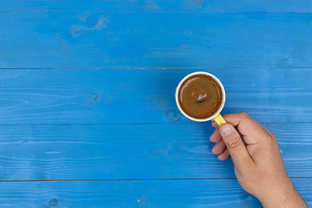 Top view of blue board background with cup of coffee in hand. 스톡 콘텐츠