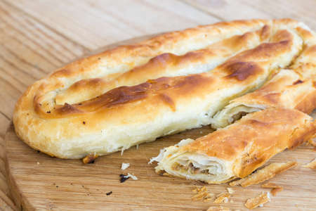 Rustic homemade burek pie with meat on the wooden background