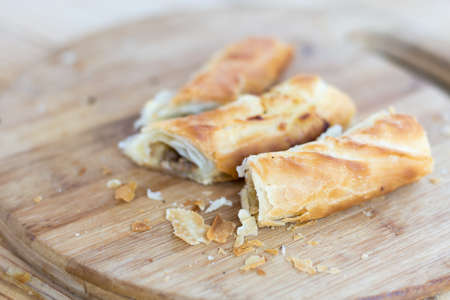 Burek with meat on the round wooden board