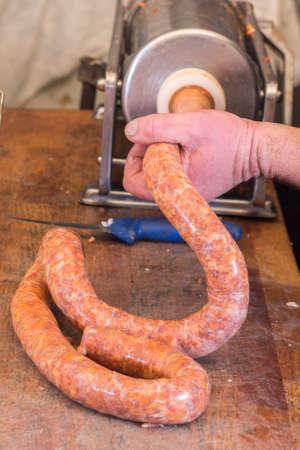 Butcher making domestic pork sausages with syringe