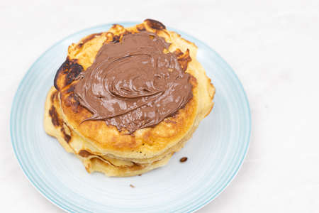 Top view of pancakes with chocolate cream on the plate.