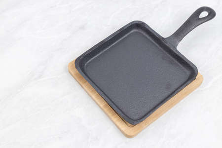 High quality square stone frying pan with wooden board and copy space.
